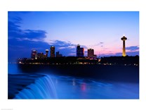 Waterfall with buildings lit up at dusk, American Falls, Niagara Falls, City of Niagara Falls, New York State, USA