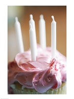 Close-up of a pink frosted cupcake with white unlit candles Fine-Art Print