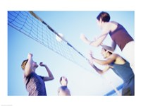 Low angle view of two young couples playing beach volleyball Fine-Art Print