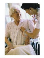 Female nurse checking a female patient's heartbeat Fine-Art Print