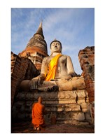 Monk praying in front of a statue of Buddha Fine-Art Print