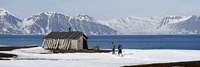 Two hikers standing on the beach near a hunting cabin, Bellsund, Spitsbergen, Svalbard Islands, Norway Fine-Art Print