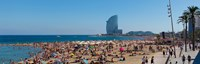 Tourists on the beach with W Barcelona hotel in the background, Barceloneta Beach, Barcelona, Catalonia, Spain Fine-Art Print
