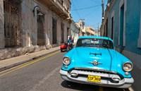 Cuba, Camaquey, Oldsmobile car and buildings Fine-Art Print