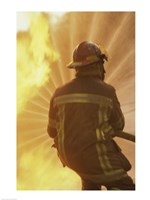 Rear view of a firefighter extinguishing a fire Fine-Art Print