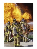 Rear view of a group of firefighters extinguishing a fire vertical Fine-Art Print