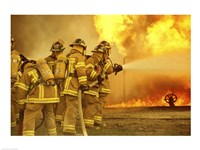 Rear view of a group of firefighters extinguishing a fire Fine-Art Print