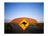Kangaroo sign on a road with a rock formation in the background, Ayers Rock Fine-Art Print