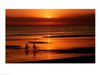 Silhouette of a young couple cycling on the beach Fine-Art Print
