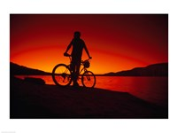 Silhouette of a man standing with a bike, Lake Powell, Utah Fine-Art Print