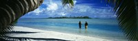 Rear view of two native teenage girls in lagoon, framed by palm tree, Aitutaki, Cook Islands. Fine-Art Print