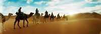 Tourists riding camels through the Sahara Desert landscape led by a Berber man, Morocco Fine-Art Print