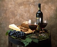 Still life of wine bottle, wine glasses, cheese and purple grapes on top of barrel Fine-Art Print