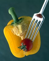 Close up of half yellow pepper with cherry tomato in center on fork tines Fine-Art Print
