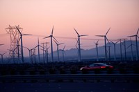 Car moving on a road with wind turbines in background at dusk, Palm Springs, Riverside County, California, USA Fine-Art Print