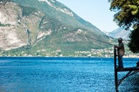 Man Fishing from Dock on Edge of Lake Como, Varenna, Lombardy, Italy Fine-Art Print