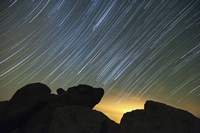 Light pollution illuminates the sky and star tails above large boulders Fine-Art Print