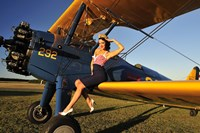 1940's style pin-up girl sitting on the wing of a Stearman biplane Fine-Art Print