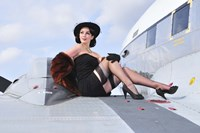 Glamorous woman in 1940's style attire sitting on a vintage aircraft Fine-Art Print