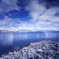 Tranquil lake and rocky shore against cloudy sky, Sardinia, Italy Fine-Art Print