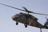 A UH-60 Blackhawk Medivac helicopter flies over Camp Warhorse Fine-Art Print