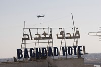 An AH-64 Apache in flight over the Baghdad Hotel in central Baghdad, Iraq Fine-Art Print