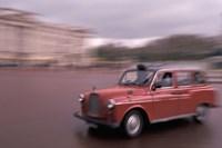 Cab racing past Buckingham Palace, London, England Fine-Art Print
