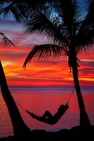 Woman in hammock, and palm trees at sunset, Fiji Fine-Art Print