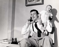 1950s Father Holding Baby While On The Phone Fine-Art Print