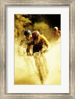 Young men riding bicycles through water Fine-Art Print