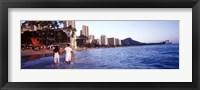 Rear view of a couple wading on the beach, Waikiki Beach, Honolulu, Oahu, Hawaii, USA Fine-Art Print